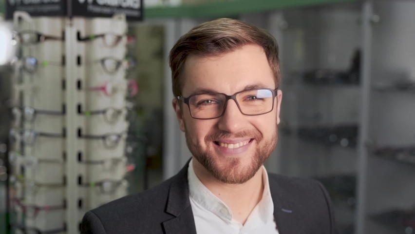 Handsome man measures glasses for vision in store | Shutterstock HD Video #1063277701