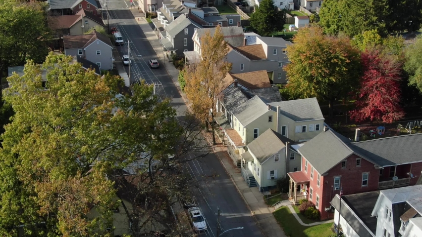 Aerial tilt up reveals two story homes in small town community neighborhood. Cars on quiet street. Establishing shot in Northeast United States of America, USA.