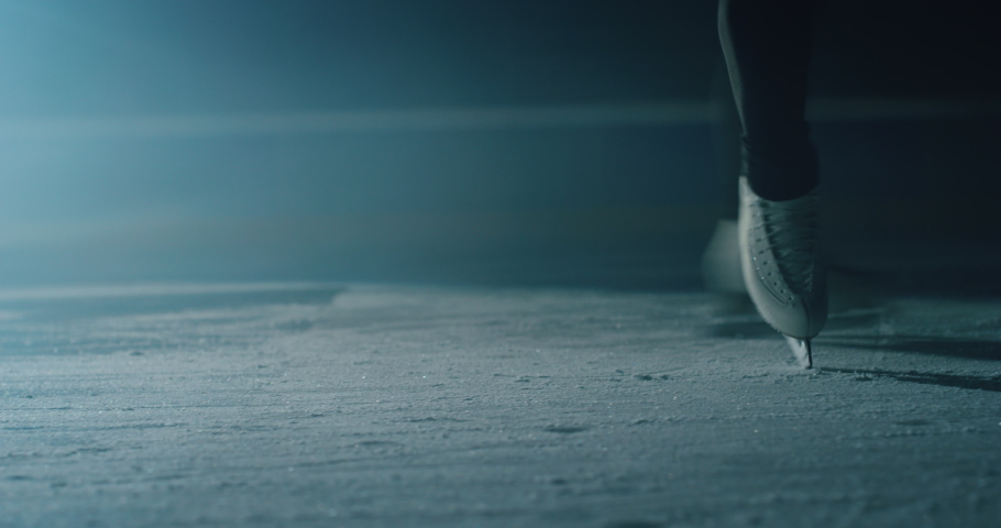 Cinematic close up shot of female figure skater's skating shoes while performing a woman's single choreography on ice rink during a competition. Concept of perfection, precision, freedom, passion. | Shutterstock HD Video #1063295923