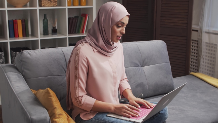 Young and attractive Muslim woman in hijab works at home using laptop computer. Middle Eastern freelancer or student on the couch. Royalty-Free Stock Footage #1063307092