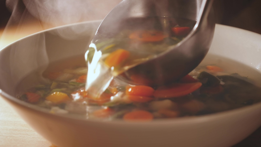 Pour a ladle of minestrone soup. Vegetarian soup dish is on table. Vegetarian healthy meal for dinner. Ready vegetable meal for lunch, hot and cozy soup for dinner at home. Soup with potatoes, carrots