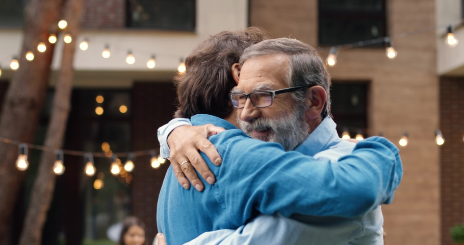 Cheerful happy Caucasian man meeting with old father and hugging at back yard of house. Family dinner outdoors on background. Senior dad with adult son in hugs. Generations. Two men embracing.