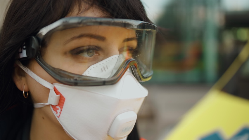 Macro: Paramedic looks away wearing protective goggles and respirator | Shutterstock HD Video #1063321105