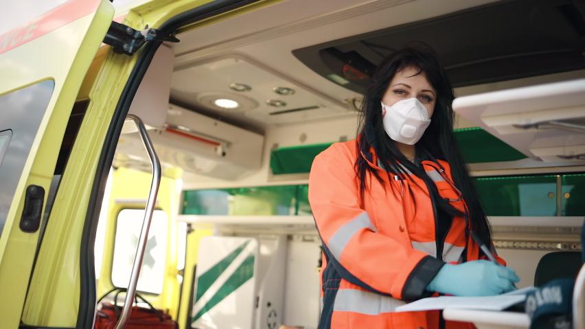Young female paramedic fills documents inside ambulance vehicle | Shutterstock HD Video #1063321714