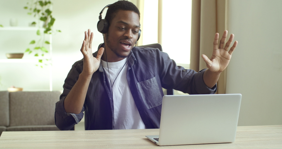 Black mixed race african businessman student lonely guy sitting at table in home office watching music videos online on internet uses laptop wears headphones listening to modern music dancing sings | Shutterstock HD Video #1063331533