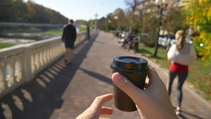 First-person view, a man holds a disposable cup of coffee in his hands and walks down the street | Shutterstock HD Video #1063333573