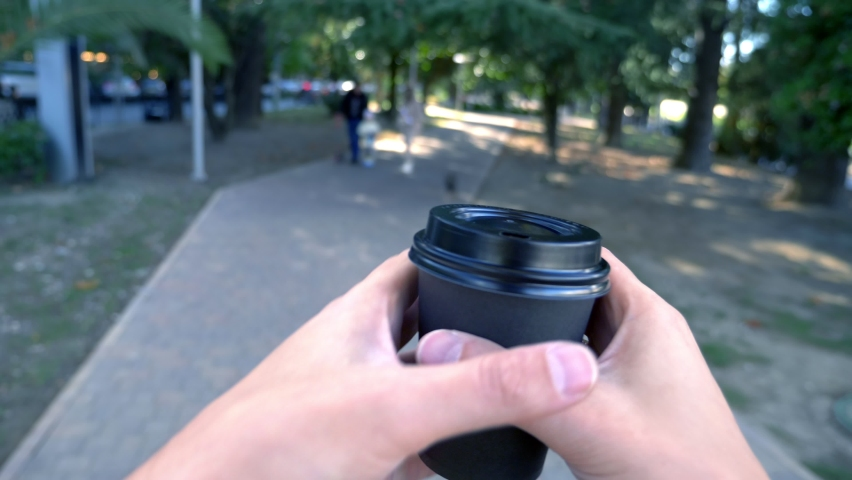 First-person view, a man holds a disposable cup of coffee in his hands and walks down the street | Shutterstock HD Video #1063333582