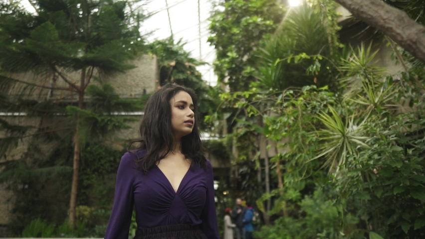Young attractive indian woman is walking through greenhouse surrounded by greenery touchin the tree looking around slowmotion