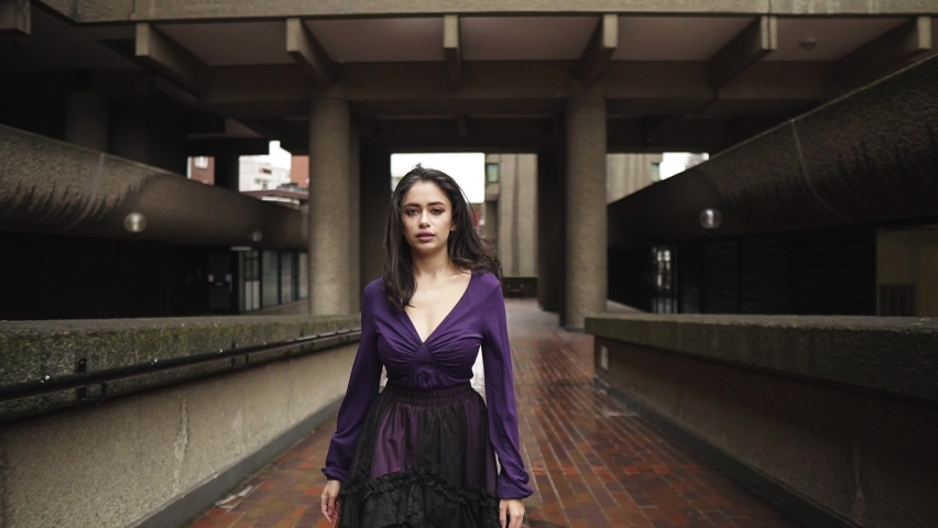 Attractive young middle eastern woman surrounded by beautiful architecture walking towards the camera in heels and purple gothic dress slowmotion