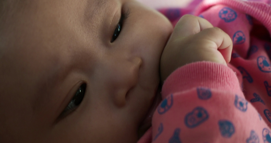 Cute few months old Asian baby girl with puffy cheeks looking at camera Royalty-Free Stock Footage #1063344850