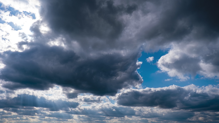 Timelapse of Gray Cumulus Clouds moves in the Blue Sky under Sun. Dramatic cloudscape timelapse. Sun rays shine through the clouds and change shape. Cirrus clouds. Majestic Amazing Sky. Cloud space