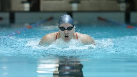 Athlete woman swims butterfly technique in indoor lap pool and preparing for olympic games. Front view video showing endurance, sport, professional swimming.
