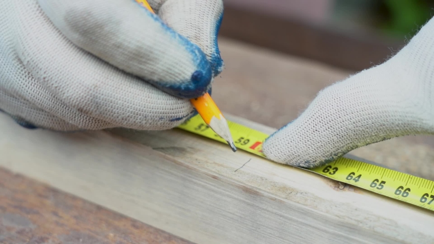 Measure the length of the tape measure. Make a mark with a pencil. Measuring tape measure small Board of wood | Shutterstock HD Video #1063354729