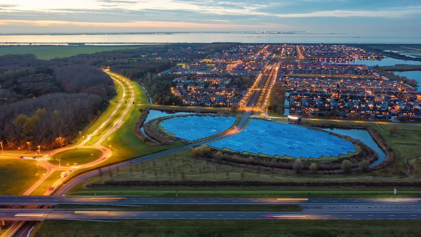 Modern sustainable residential neighbourhood in the city of Almere, The Netherlands, with solar panels farm powering city heating. Evening traffic on the roads. Aerial Hyperlapse shot at dusk. | Shutterstock HD Video #1063355212