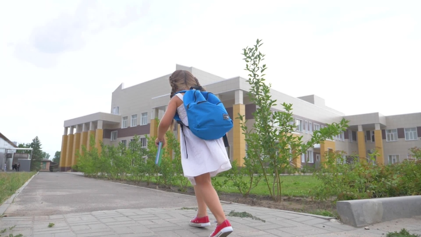 A small schoolgirl with a backpack and a book runs through the Park to school. A girl with a school backpack hurries to class. Educated children. | Shutterstock HD Video #1063355278