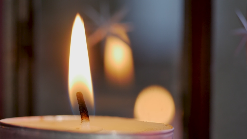 Close up view footage of igniting a candle in the dark, candle position on the left of the frame. Cozy home interior decor, burning candles hygge, decoration and christmas concept - candles burning | Shutterstock HD Video #1063366960