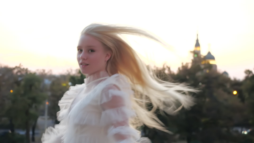 Young european blonde girl with long silky hair in white stylish dress in a hurry in glowing city night lights. Beautiful teenage lady happy in evening walking, rushing running to date at party