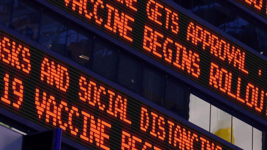 NEW YORK - Close-up view of a fictional Times Square stock market news ticker reporting that a COVID-19 Coronavirus vaccine was approved and rollout has begun. | Shutterstock HD Video #1063374622