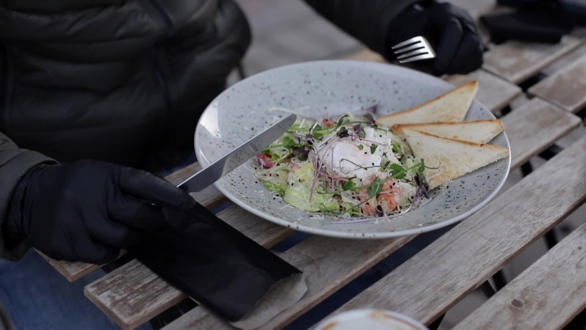 Close up of man in black gloves hold cutlery. Cafe concept during qurantine. Food outdoors in protective gloves. Fresh vegan salad with shrimps | Shutterstock HD Video #1063375171