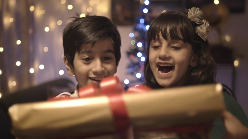Two well dressed adorable young kids are smiling and receiving their Christmas present in a decorated house. Happy and elated cute girl and boy accepting the gift box from parents  Royalty-Free Stock Footage #1063380223