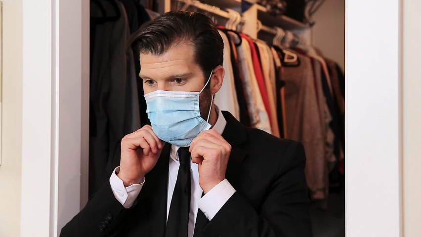 Handsome young caucasian professional man in a business suit putting on a medical face mask. HD 30FPS.