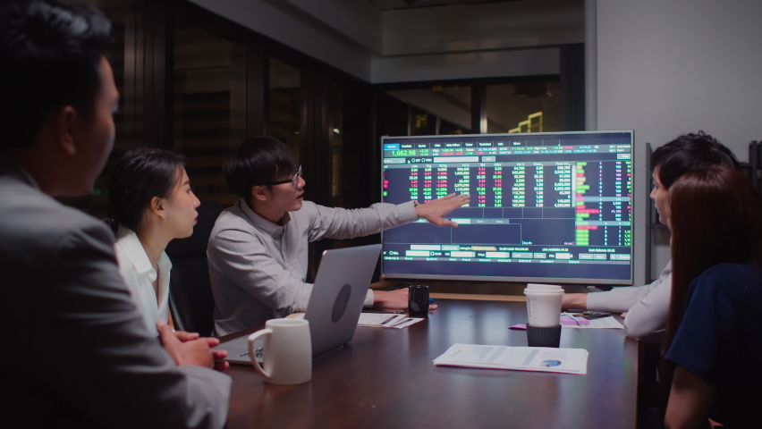 Young Asian businessman lead group of business financial team in strategic meeting presentation, work late night in office. Marketing strategy analysis, stock market trading, or corporate teamwork Royalty-Free Stock Footage #1063384678