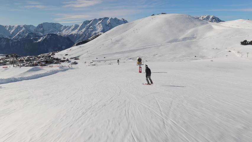 Skier going down the snowy slope, follow shot | Shutterstock HD Video #1063387924
