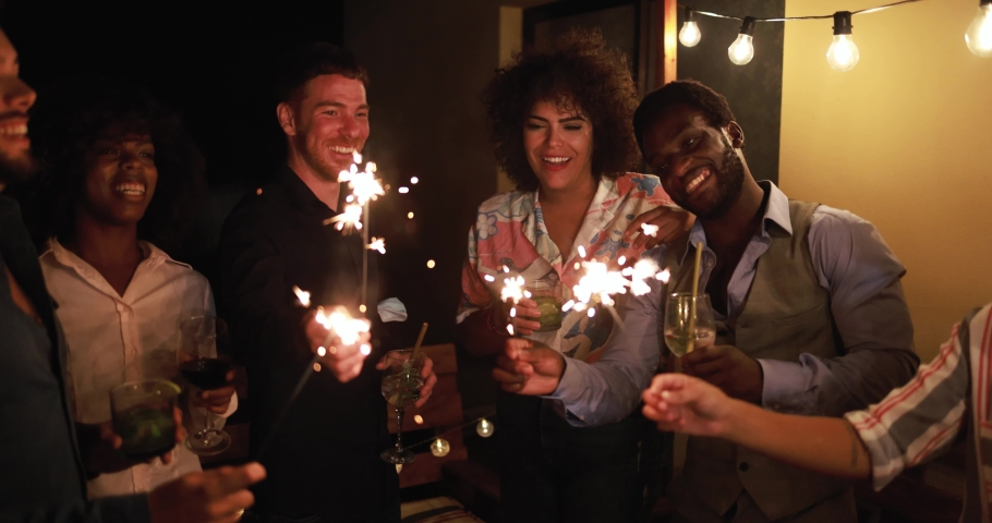 Happy friends celebrating with fireworks at new year's eve party.