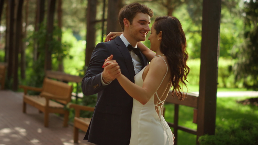 Newlyweds man and woman dancing outdoors. Closeup happy couple having first dance in park. Romantic bride and groom celebrating wedding ceremony under arch. Royalty-Free Stock Footage #1063390948
