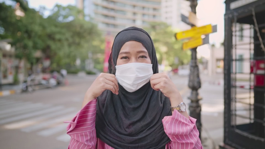 Slow motion shot of Young Asian Muslim woman put on medical face mask. standing on the street side ,city urban new normal, feel confident thumb up, COVID-19 pandemic, infectious disease protection | Shutterstock HD Video #1063401232