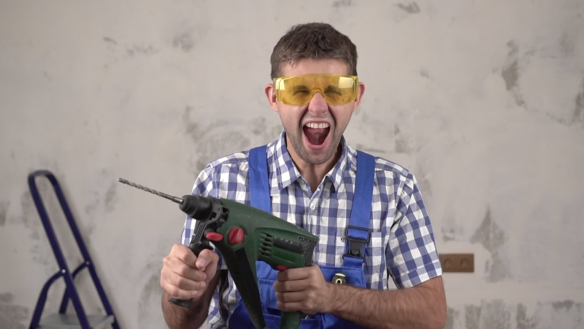 Funny crazy man construction worker shoots from an electric hammer perforator | Shutterstock HD Video #1063402849