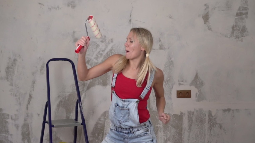 Happy young woman cheerfully dances against the background of renovation in the house, slow motion | Shutterstock HD Video #1063402858