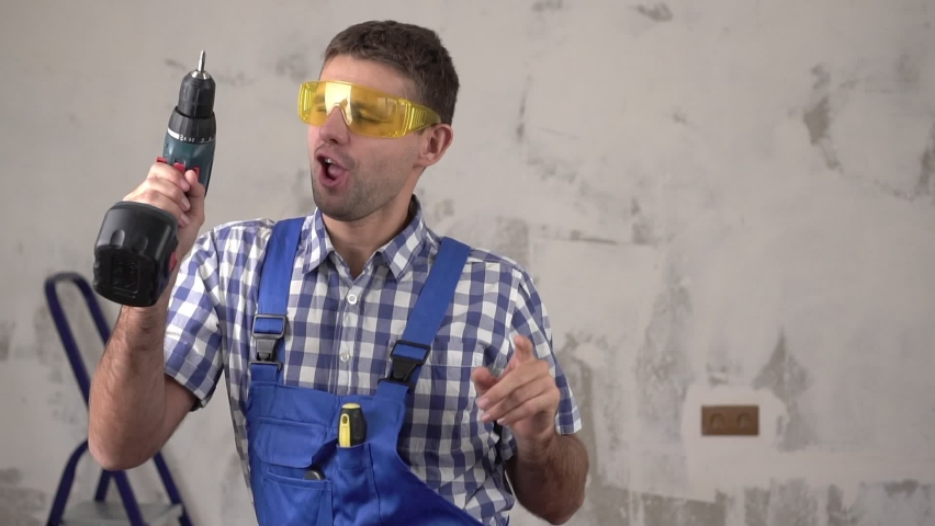 Funny cheerful and happy male builder or worker dancing on the background of repairs in the house, slow motion | Shutterstock HD Video #1063402876