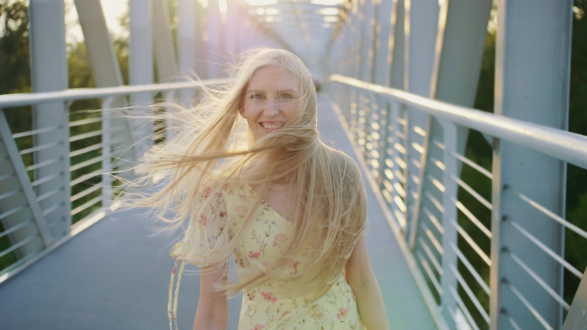 Woman looking back on bridge. Pretty blonde woman looking back at camera while running on bridge with wavy hair. | Shutterstock HD Video #1063404271