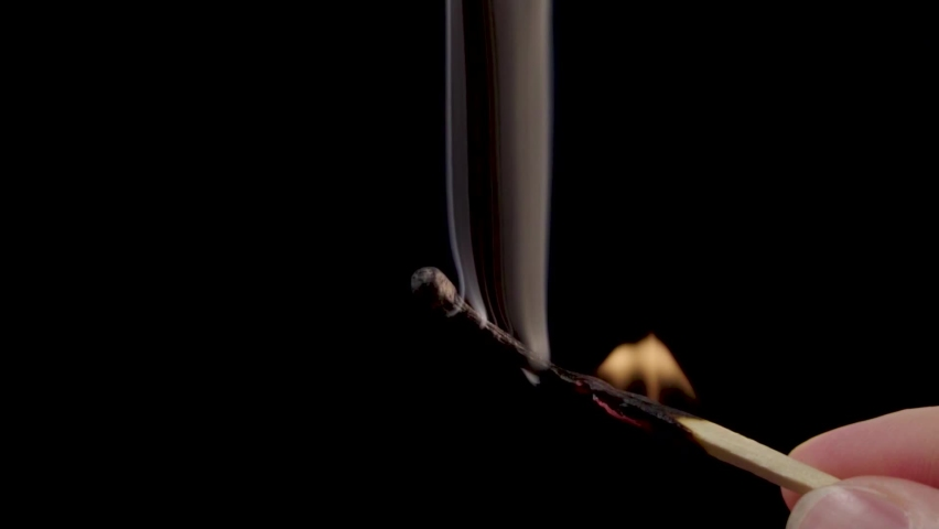 A lighted match burns with smoke on a gray background. Concept of slow-motion video with fire. The hand lights a match. | Shutterstock HD Video #1063404763
