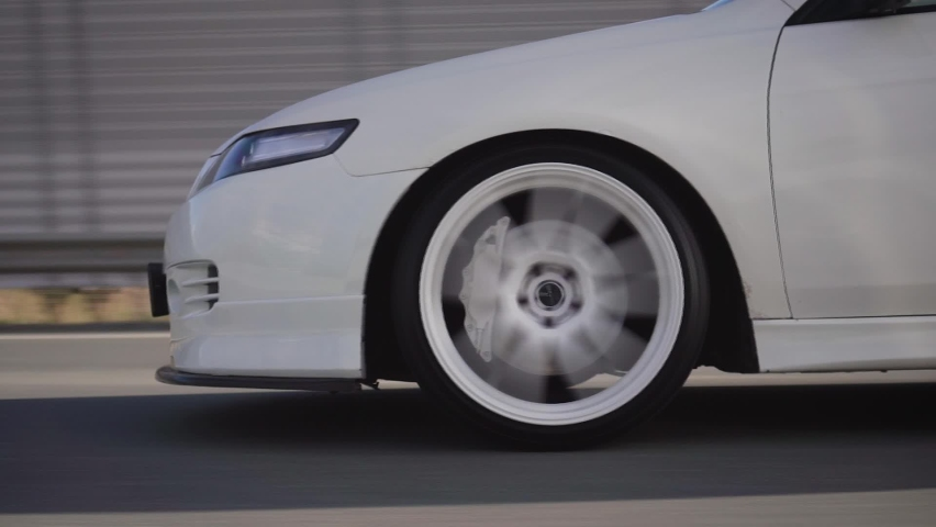 Side view of modern powerful white car rides on summer highway. Footage. Perfect auto drives fast on country road. Large sports alloy wheels with powerful brakes. Static camera, cars leave the frame. Royalty-Free Stock Footage #1063405660