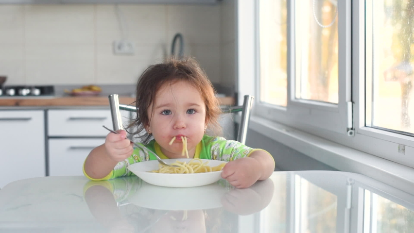 Child 3 years old girl in the kitchen eating pasta, delicious | Shutterstock HD Video #1063406014