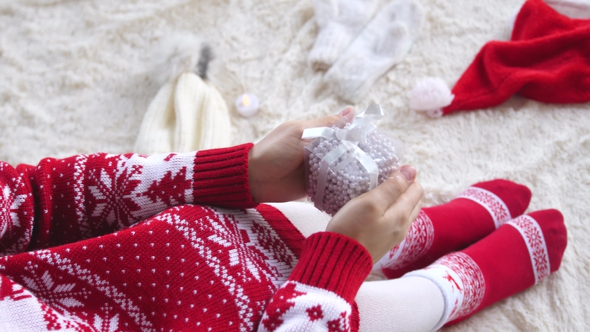 Woman Sitting on a fluffy blanket and holding Present Box. Christmas and New Year Celebration Concept. present and gift box between Christmas decorations | Shutterstock HD Video #1063410397