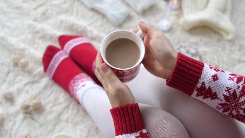 Woman hands holding a cup of hot cocoa on the background of a garland in the Christmas decorations. Cozy winter holiday concept. Woman in knitted clothes celebrating Christmas. | Shutterstock HD Video #1063410412