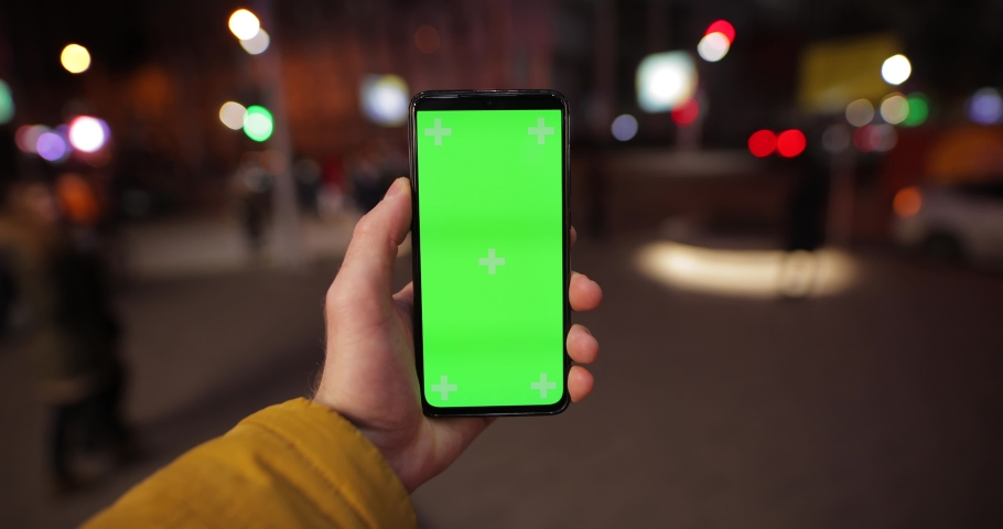 POV, male hand holding smartphone with green screen chroma key in the night city street | Shutterstock HD Video #1063415137