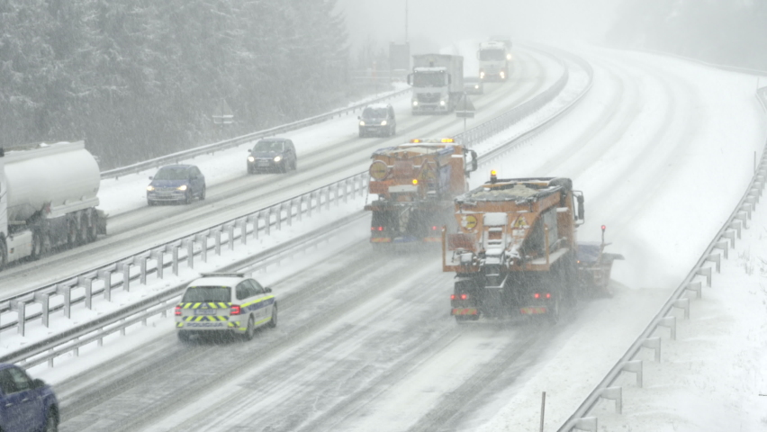 Wide locked down shot of two snow ploughs driving up the highway and clearing the snow off the road in snowfall. Royalty-Free Stock Footage #1063415944