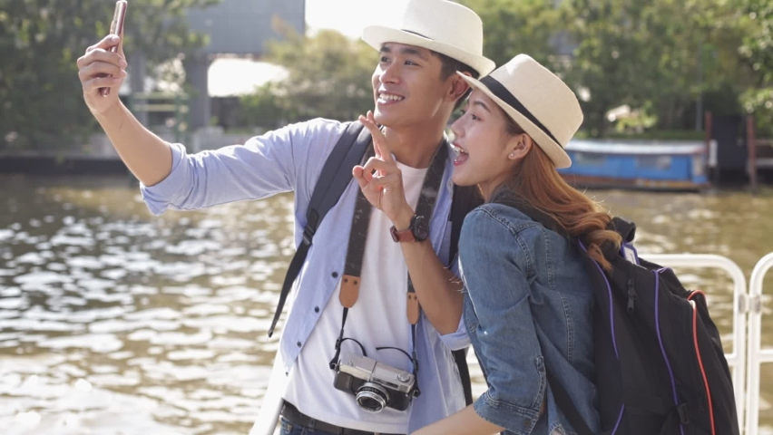 Traveler Asian couple travel in riverside Bangkok, Thailand, sweet couple taking photo  spending holiday trip in sunset. Young fun happy Asian tourist backpacker travel. Royalty-Free Stock Footage #1063416055