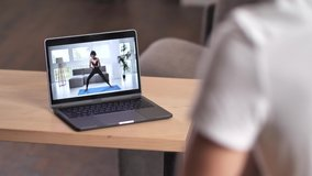 Close-up of laptop screen with live stream of joyful mixed race woman trainer practicing yoga warrior pose during online workout with male, remote home training, e-learning, healthy sport lifestyle