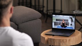 Close-up of streaming video with professional female trainer meditating in yoga lotus position during online workout with male sitting at laptop, remote home training, healthy positive lifestyle