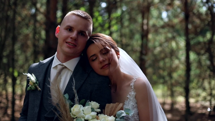 Elegant romantic newlyweds couple smiling looking at camera enjoying wedding day. Sunny background. Bride holding wedding bouquet of amazing white flowers. Dating agency. Family ties concept.  Royalty-Free Stock Footage #1063418398