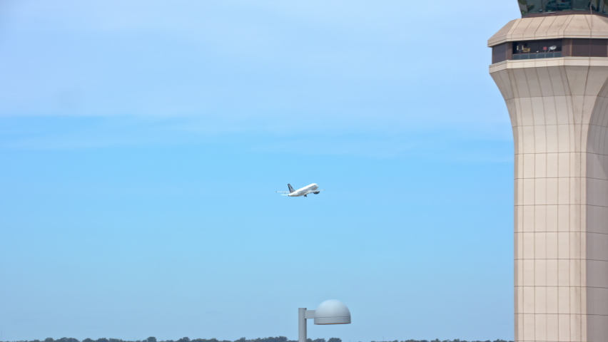 Generic Airport Air Traffic Control Tower with Departing Commercial Passenger Jet Airliner Taking Off past the ATC Communications Tower Flying into a Blue Sky on a Sunny Day | Shutterstock HD Video #1063421575