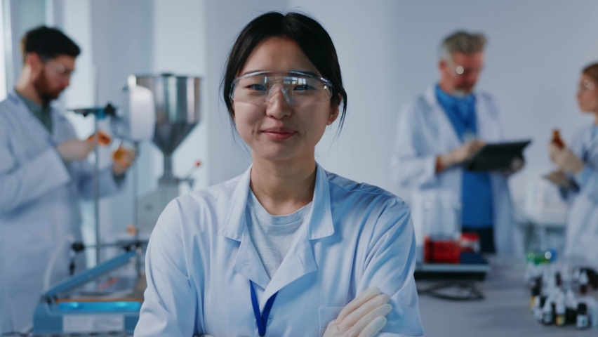 Asian portrait woman scientist with protective glasses look at camera smiling feel happy. Background team work. Microbiology pharmaceutical biochemistry medical technology. Slow motion Royalty-Free Stock Footage #1063426288