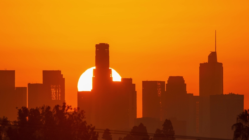 Downtown Los Angeles. Sunrise sun over city buildings silhouettes, zoom out. Timelapse, 4K UHD