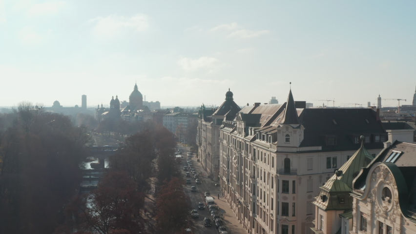 Beautiful residential street with old architecture apartment buildings by the Isa River in Munich, Germany on Sunny day, Aerial Scenic Slide left revealing City Skyline
