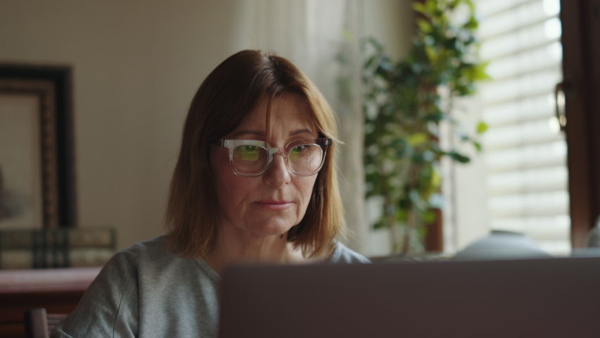 Portrait of an adult happy woman working on a laptop. Happy woman freelancer at the computer looks at the monitor. Remote work freelancer at home workplace. High quality 4k footage Royalty-Free Stock Footage #1063438030